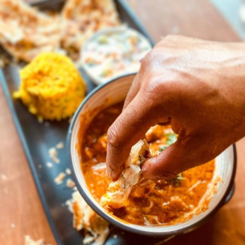 Roti dipped in curry by hand