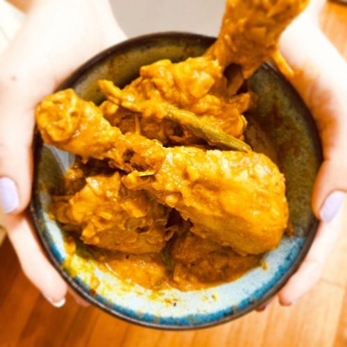 Chicken curry in a bowl held by two hands