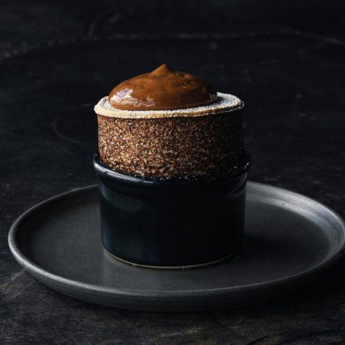 Chocolate souffle rising out of a ramekin