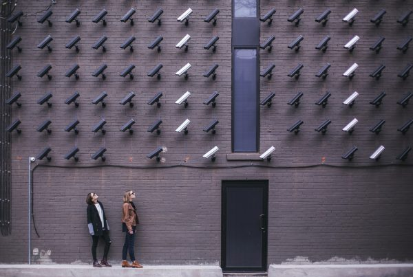 Two people being watched by a wall of security cameras