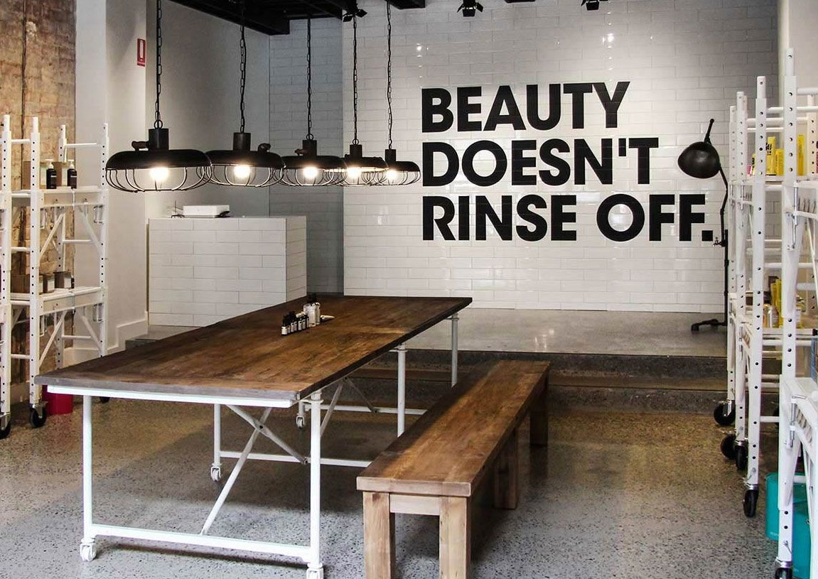 DECIEM Store - a wooden bench with white shelves and the slogan Beauty Doesn't Rinse Off on the back wall