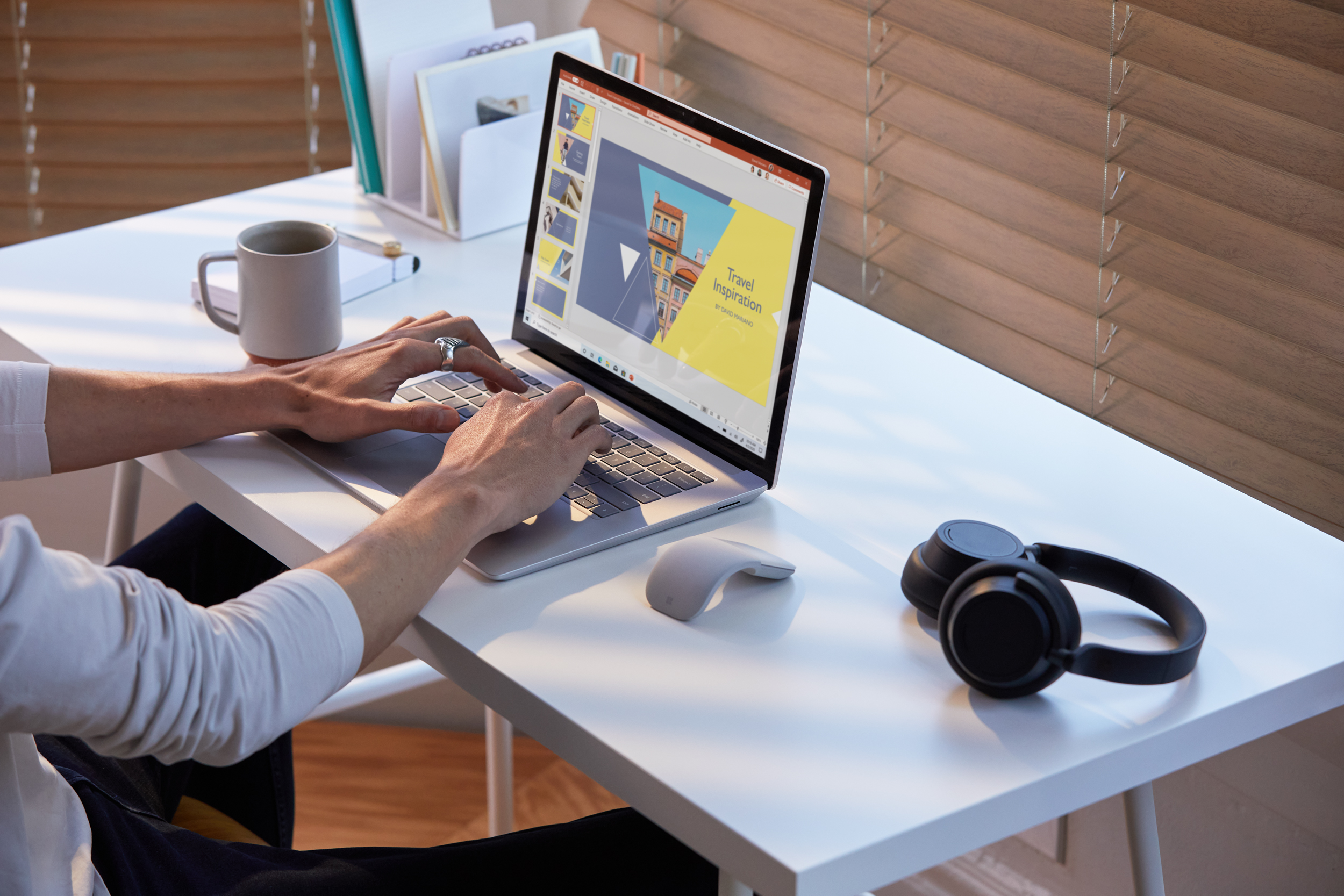 Woman working on a Surface Book at home with a pair of Surface Headphones on the desk