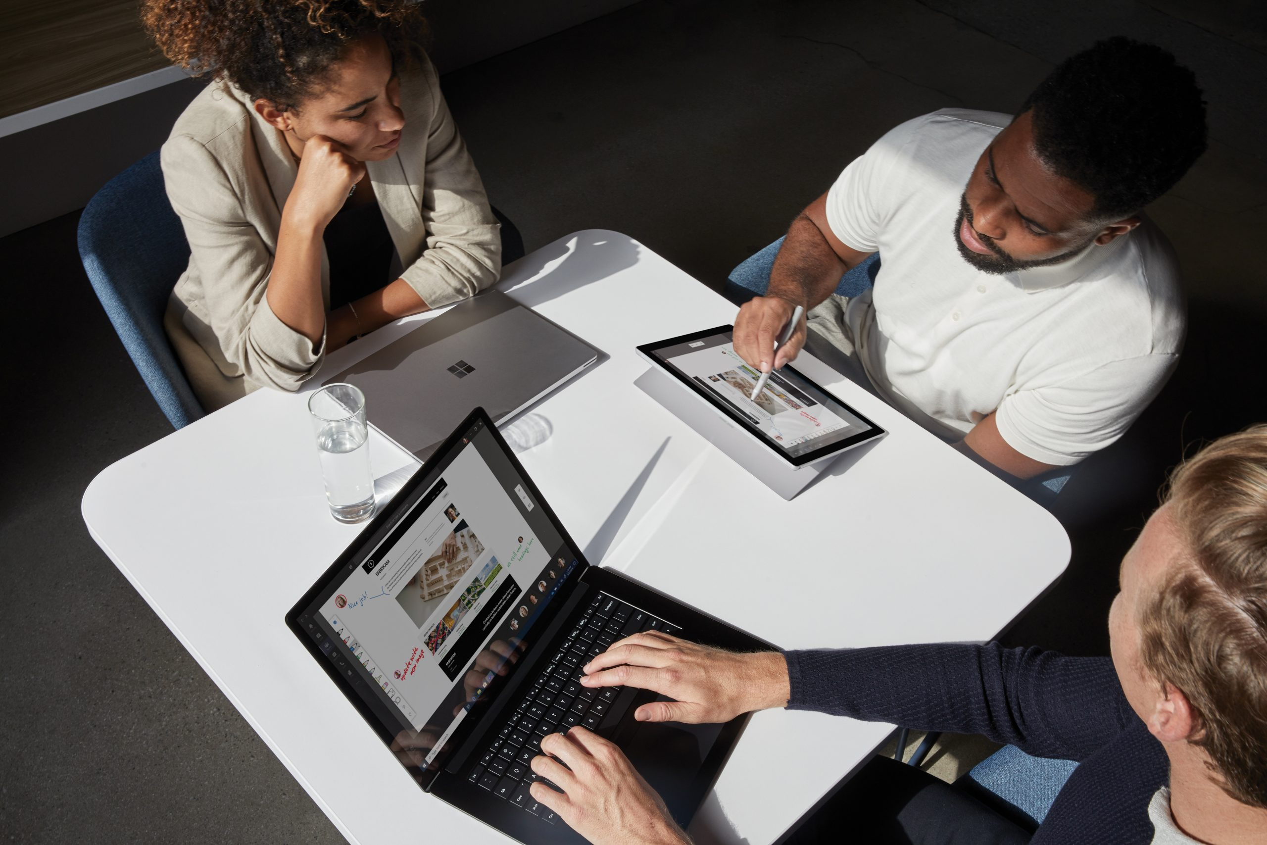 Team of 3 huddled around a small table with Microsoft Surface devices