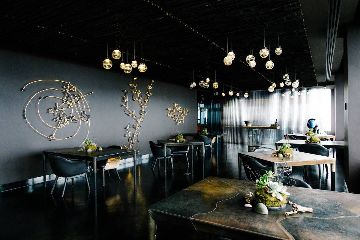 Dark, high end restaurant with small tables decorated with native plants