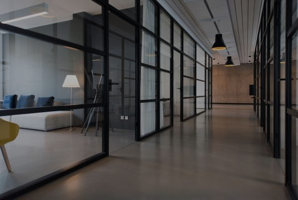 A modern office space hallway with offices on each side