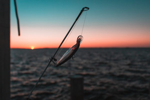 A lure on the end of a fishing rod hanging over the ocean at sunset